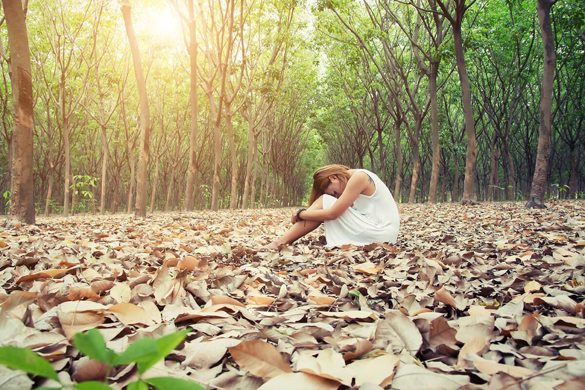 kobieta-w-lesie-siedzi-na-liściach. Depresja - jak odróżnić ją od jesiennego smutku