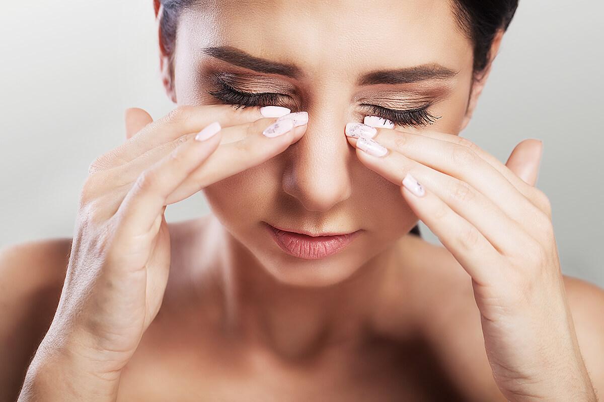 Kobieta dotyka dłońmi nosa - Polipy w nosie i inne przyczyny trudności w oddychaniu