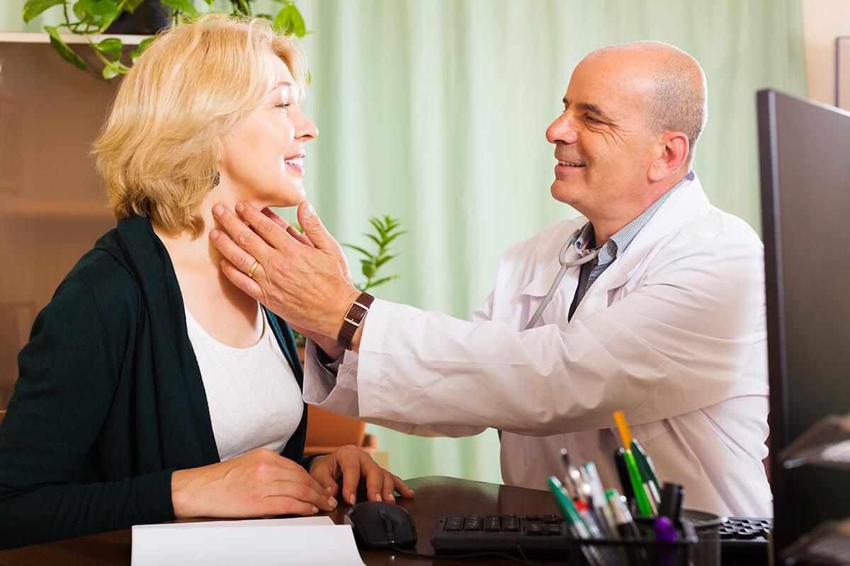 Lekarz bada tarczycę pacjentki -Jakie choroby leczy endokrynolog