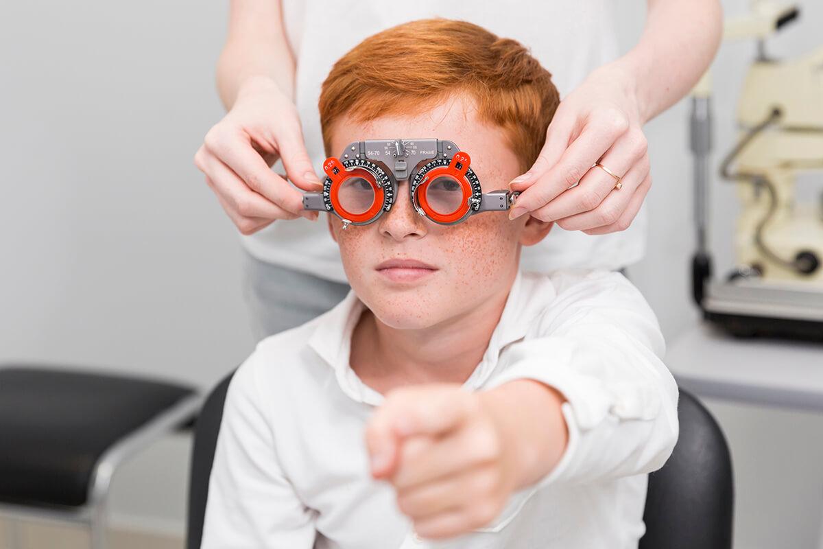 Chłopiec bada wzrok u okulisty - nadwzroczność u dzieci
