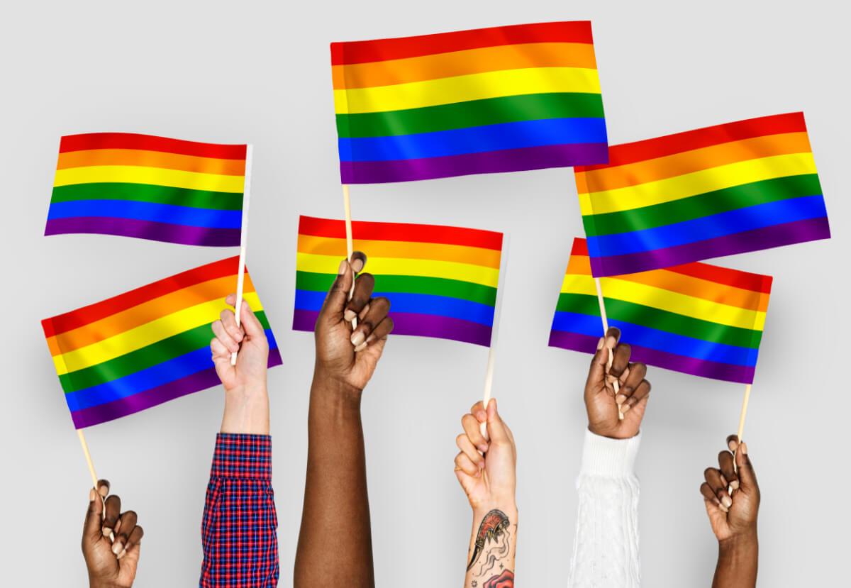 Dłonie z tęczowymi flagami - Problemy osób lgbt na świecie