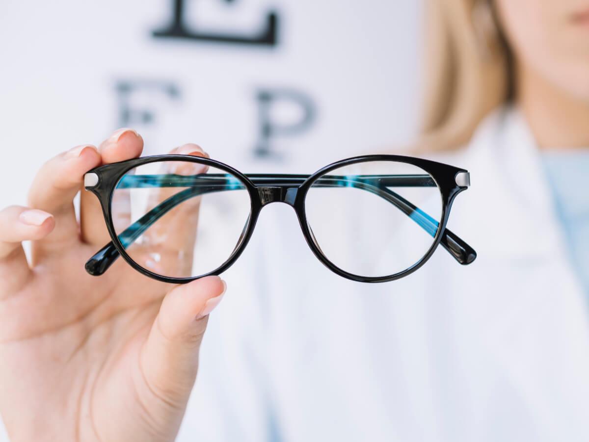 Okulary w dłoni okulisty. dobór okularów korekcyjnych